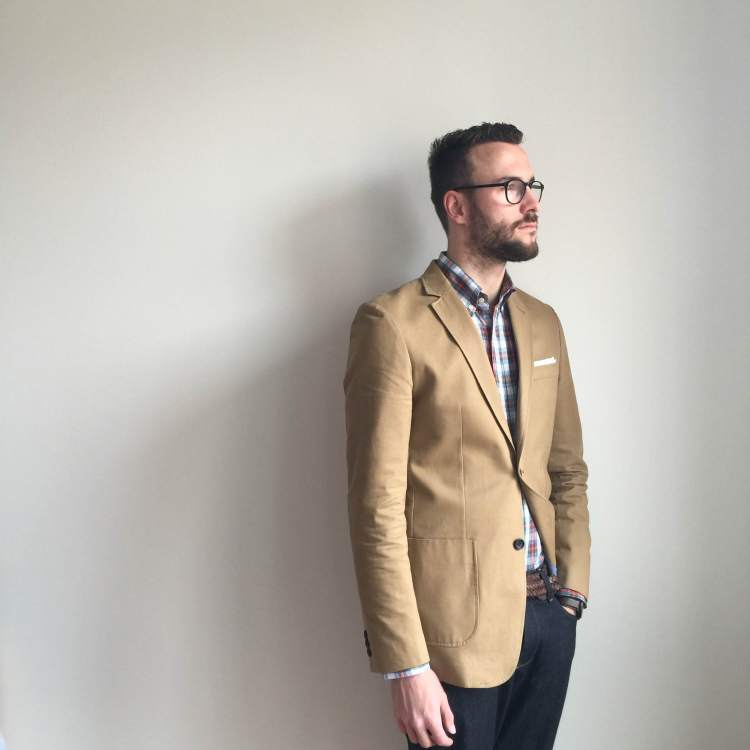 On the lookout for spring. Shirt by Gustin. Khaki Travel Jacket by Combat Gent. Pocket square by Banana Republic. Glasses by Warby Parker. Photo credit: Liz Todd.