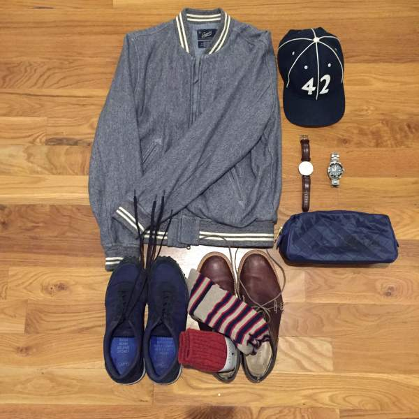 Travel essentials for a cross-country trip. Russel Baseball Jacket by Grayers. Navy sneakers by GREATS Brand. Socks by American Trench. Leather chukka boots by Timberland. Leather watch by Daniel Wellington. Dive watch by Invicta. Vintage ballcap by Goorin Brothers. Dopp kit by Baxter of California.