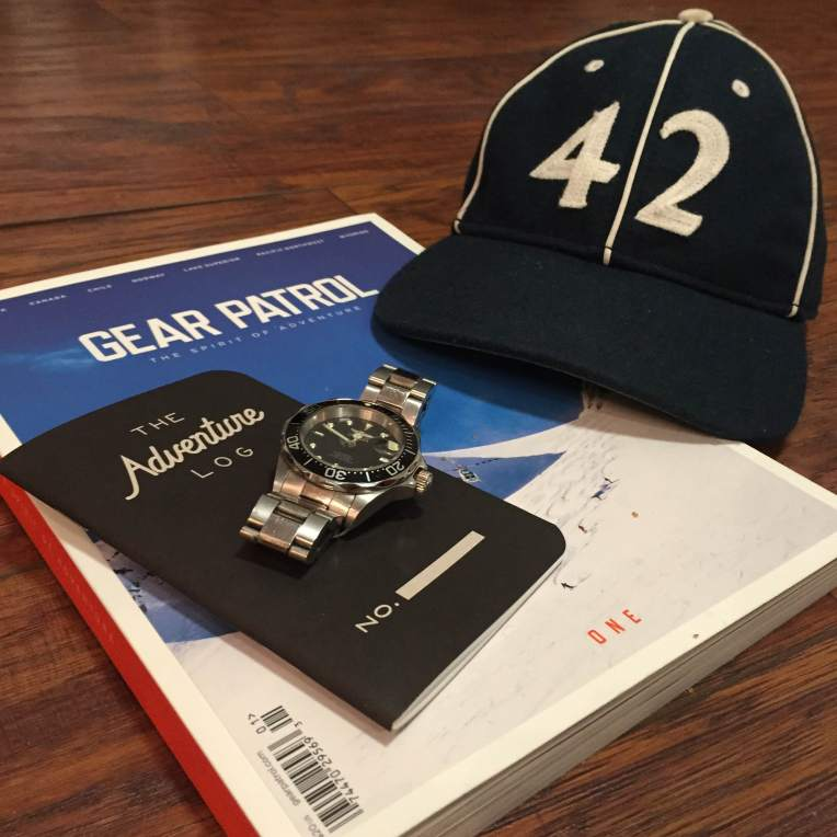 Travel gear for the road ahead. Vintage ballcap by Goorin Brothers. Adventure Log by Word Notebooks. Stainless steel dive watch by Invicta. Print magazine by Gear Patrol