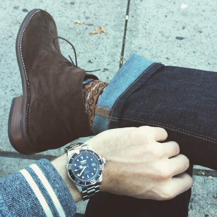 The boot hits higher on the ankle, a refined touch that stands out --in a good way. Fair Isle socks by American Trench. Baseball jacket by Grayers. Dark denim by Mott & Bow. Watch by Invicta.