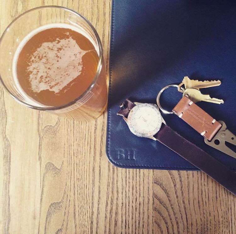 Another way to accessorize a monogrammed Issara leather laptop sleeve -- with a tasty brew after a hard day's work. Watch by Timex. Horween Chromexcel Color No. 8 watch strap by Form-Function-Form. Tan leather keychain by Apolis.