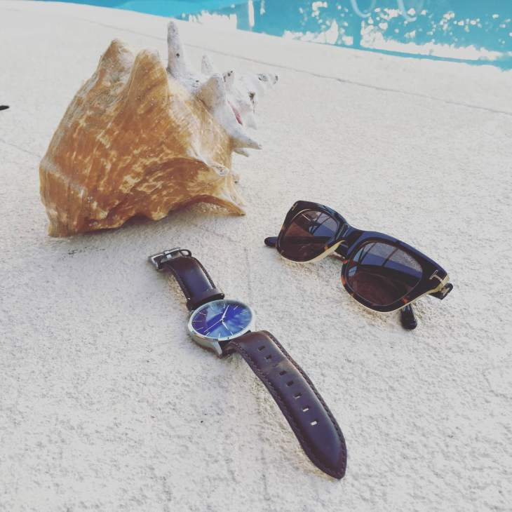 Relaxing poolside with a few choice style essentials. Brown leather watch by MVMT Watches. Sunglasses by Tom Ford.