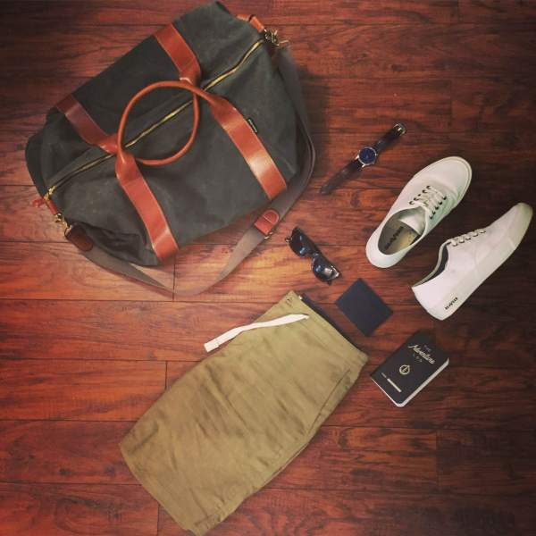 Easygoing gear for a weekend of adventures. Waxed Voyager Weekender by Owen & Fred. Legend Sneakers by SeaVees. Stringer Dune Shorts by Bridge & Burn. Sunglasses by Tom Ford. Navy leather card case by Issara. Brown leather watch by MVMT Watches.