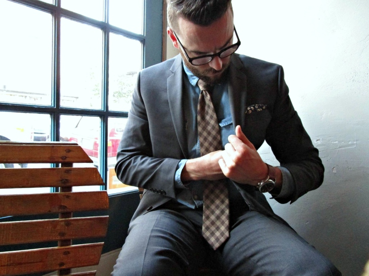 On the go with a comfortable, slim-fitting and flexible suit jacket. Denim shirt C/O Forever21 Men. Plaid wool tie and patterned pocket square by Ties.com. Waterbury Chrono by Timex x Red Wing Heritage.