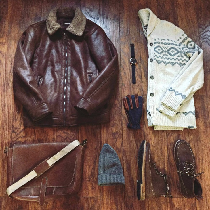 Tough essentials to fight the cold. Faux Shearling Aviator Jacket by Johnston & Murphy. Snowbridge Cardigan by Eddie Bauer. Buxton Boots by G.H. Bass. Calypso Watch by MVMT Watches. Ranger Gloves by Grifter Company. Cap by Everlane. Messenger by Brothers Leather Supply.